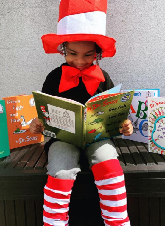 young girl smiles reading a book